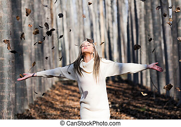 Beautiful blonde girl with falling leaves in the autumn park...