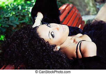 Young African woman siting on bench in park - Young...