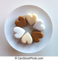 Six heart-shaped pudding pieces on white plate