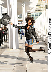 Young pretty black woman jumping in the street with a...