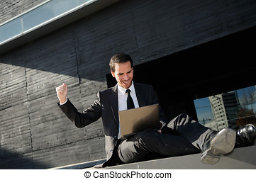 A businessman sitting on the floor with a laptop computer,...