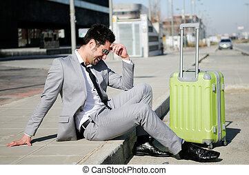 Man dressed in suit and suitcase sitting on the ground in...
