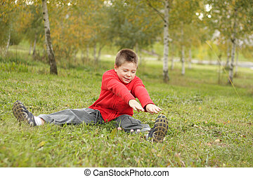 Outdoor exercises inclination to left - Boy sitting on grass...