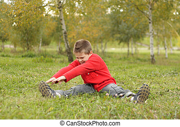 Outdoor exercises inclination to right - Boy sitting on...