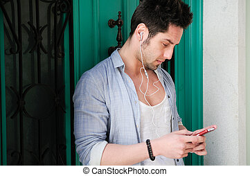Portrait of handsome man in urban background listening to...