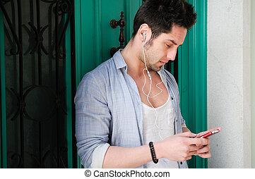 Portrait of handsome man in urban background listening to...