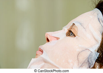 Portrait in Profile woman applying rejuvenating facial mask...