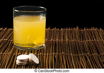 Vitamins pills soluble in water Glass of water with vitamins...