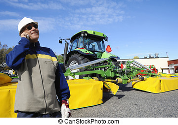 farmer with tractor and mowers - a modern farmer talking in...