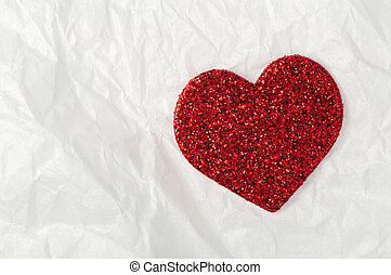 Shiny red heart on white paper