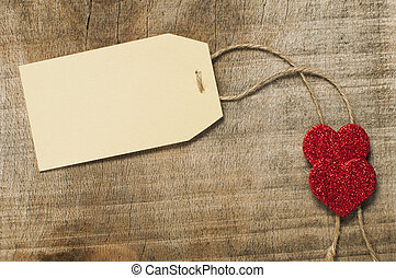 Paper label with rope and red hearts on wooden background