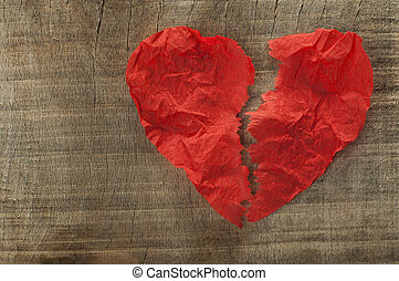 Heartbreak made of curled red paper on wooden board
