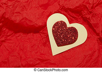 Red heart brocade shape on a wrinkled paper