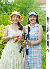 Female gardeners with garden tools at yard