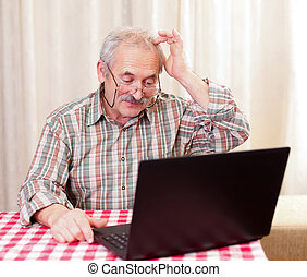What to click next? - Elderly man using the laptop at home.