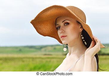 Beautiful brunette woman in hat in summer day