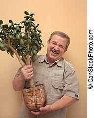 Cheerful elderly the man with a flowerpot
