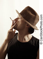 Portrait of a young man in hat with cigarette - Portrait of...