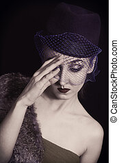 Retro portrait of a beautiful young woman in  hat with  veil