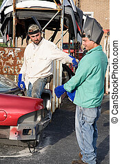 Scrap Metal Workers - Two metal workers in the scrap metal...