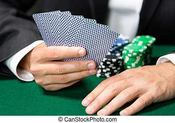 Gambler playing cards with chips on the table