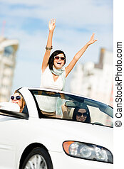 Lovely teenager with her hands up in the cabriolet