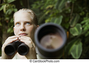Pretty Woman with Binoculars in the Rain Forest