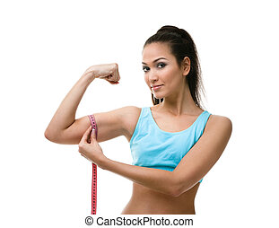 Sporty woman measures her bicep with measuring tape,...