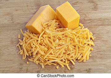 180 cheddar cheese - Shredded cheddar cheese on a brown...