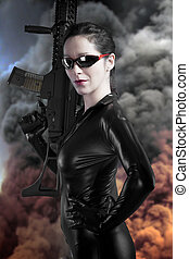 Sexy brunette woman in latex jumpsuit with heavy gun over smoke background