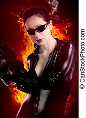 Sexy brunette woman in latex jumpsuit with heavy gun over fire background