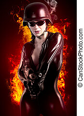 Sexy brunette woman in latex jumpsuit with heavy gun and helmet over fire background