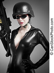 Sexy brunette woman in latex jumpsuit with heavy gun and...