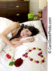 Happy beautiful woman in bed with romantic gifts from boyfriend