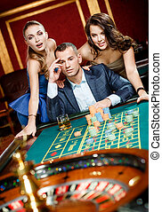 Man with two girls playing roulette at the gambling house -...