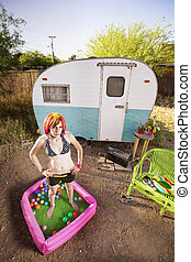 Woman outside a trailer - Woman standing in a play pool...