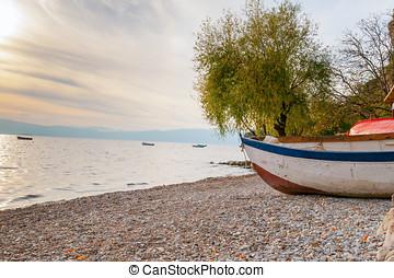 White boat at the stony beach in Ohrid lake coast Macedonia...