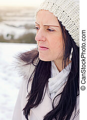 worried woman in snow covered fields at sunset