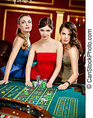 Three women place a bet playing roulette at the gambling...