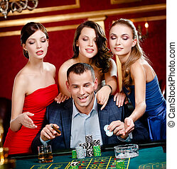 Man surrounded by women gambles roulette - Man surrounded by...