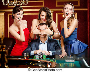 Girls cover the eyes of the gambler playing roulette at the...