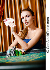 Female gambler at the poker table with cards and chips