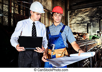 construction - An architecture and worker at a manufacturing...