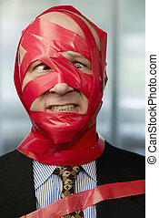 Red Tape - Cross-eyed businessman wrapped in red tape