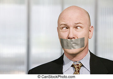 Cross-eyed businessman muzzled with duct tape - Cross-eyed...