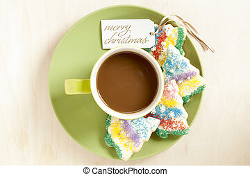 hot chocolate in a cup in green saucer with christmas cookies
