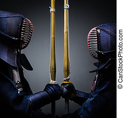 Two kendo fighters opposite each other with shinai - Two...