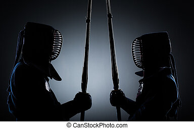 Two kendo fighters opposite each other with shinai Japanese...