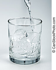 Water flowing onto ice in glass - Water stream flowing into...