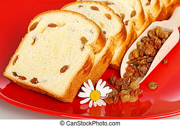 Macro of sweet loaf slices with raisins on red plate
